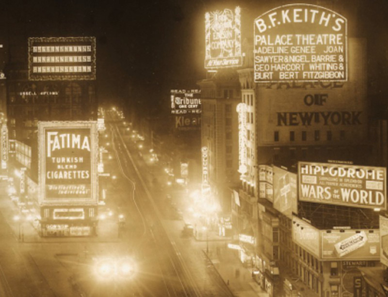 historical image of a street with lighted signs at night